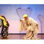 Two actors performing on stage in Japanese kimonos and construction hard hats