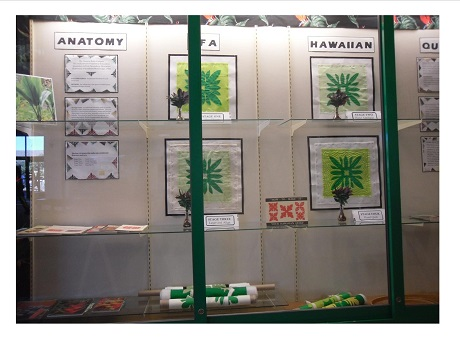 Photo of pieces of Hawaiian quilt at various stage of completion in Kapolei Public Library 1st-floor display case